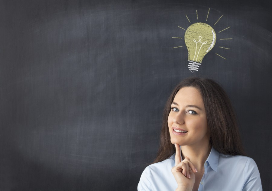 Smiling businesswoman standing in front of chalkboard with light bulb drawn above her head. Concept about ideas.